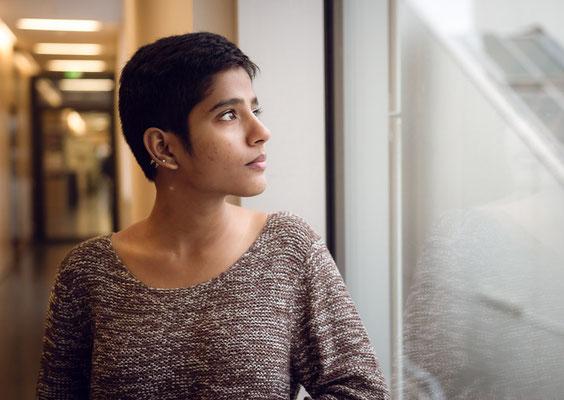 Portrait einer Jungen Frau die aus einem Fenster schaut