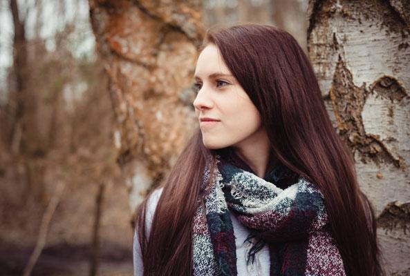Frau mit braunen Haaren vor Birken in Erlangen