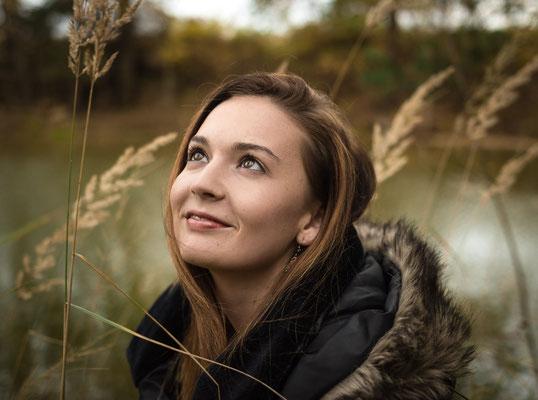 Brünette Frau blickt sanft in den Himmel vor einem See