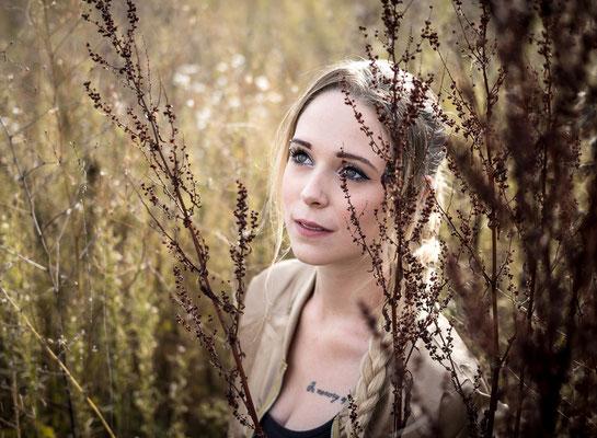 Junge Frau hinter Gräßern in Frochheim