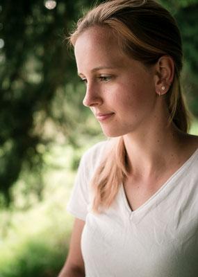 Portrait einer blonde Frau in einem ruhigen Wald