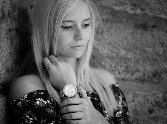 Junge Frau fasst sich an ihre Uhr vor einer Steinwand