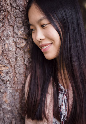 Fröhliche Asiatische Frau vor Baumrinde