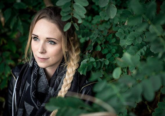 Blonde Frau versunken in grüne Blätter in Frochheim