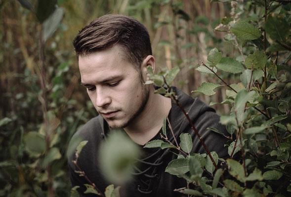Junger trauriger Mann auf einer Wiese hinter Gestrüpp
