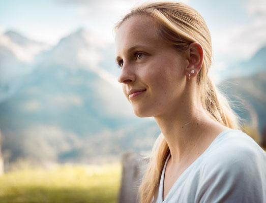 Portrait einer blonde Frau vor Bergen