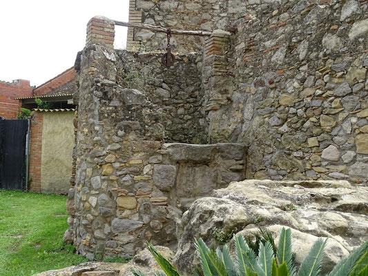 Bauerhof mit Ziehbrunnen vor der Kirche. Davor ein Felsen, der vom Wasser des früher hier vohandenen Sees ausgespült wurde