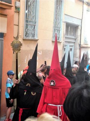 """...rot und schwarz gewandete Kapuzenmänner führen die verschiedenen Gruppen der """"Bruderschaften"""" an, die die Prozession neben der Perpignaner Bruderschaft mitgestalten"""
