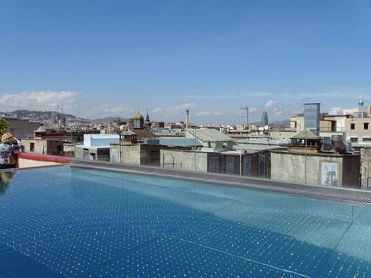 Blick von der Dachterrasse über das Schwimmbad hinweg. Man kann links die Türme der Sagrada Familia und rechts den Torre Agbar erkennen