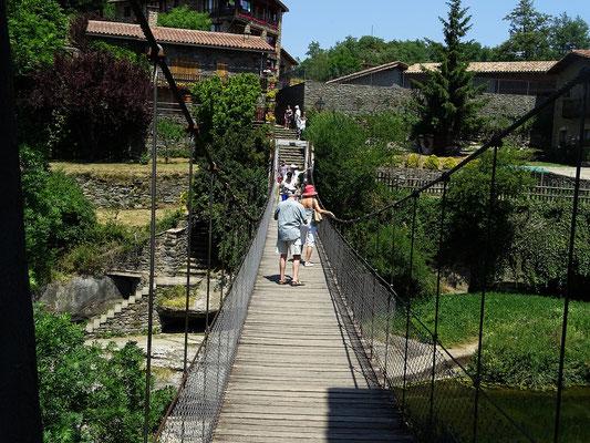Über eine schwankende Hängebrücke geht es in den auf Felsen (lat. rupes) gebauten Ort, daher der Name