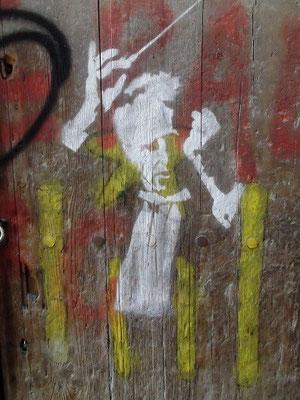 Ein Sprayerbild auf einem Holztor gegenüber
