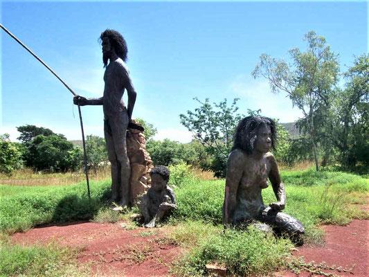 Indigenous People in ihrer ursprünglichen Landschaft und Lebensweise (Skulpturen). Nach dem Traumzeitmythos der Indigenen sind aus den Schuppen eines Barramundi-Fisches Diamanten entstanden