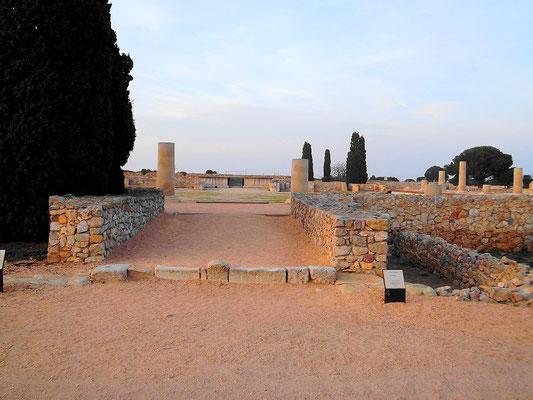 """Der Tempel der """"Kapitolinischen Trias"""" im Hintergrund mit vorgelagertem Opferpodium. Im Vordergrund rechts: Reste - beginnend - Reste einer Ladenzeile"""
