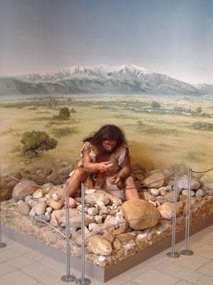 Mensch von Tautavel bei Steinbearbeitung (Museum Tautavel)