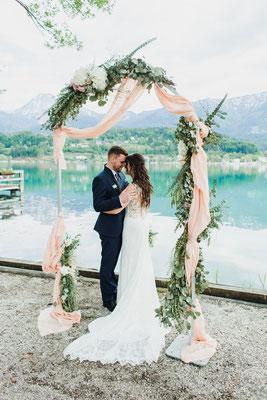 Hochzeitspaar unter einem Blumenkranz am See