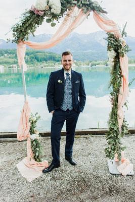 Bräutigam am Se unter einem Blumenkranz
