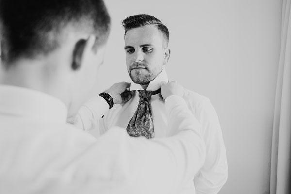 Trauzeuge beim Krawatte umbinden des Bräutigams
