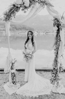 Braut am See unter einem Blumenkranz