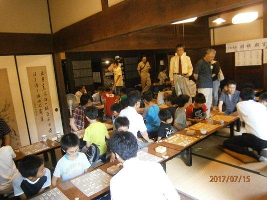 (遠くてすみません)黄色いシャツにネクタイのMSG総統先生ととなりの京谷先生は、こどもたちにプロ棋士指導対局の案内をしていらっしゃいました。