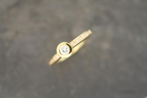 Ring aus Gelbgold mit Brillanten in Zargenfassung (Mittelstein) und im Verschnitt gefasst