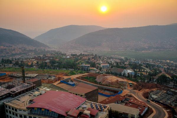<b>Nebliger Sonnenuntergang in Kigali: Sebastian Krantz</b> Im Vordergrund wird das Fundament für neue Türme gelegt und im Hintergrund ist das Tal Nyabogogo zu sehen, das den Zentralen Busbahnhof Kigalis beherbergt.