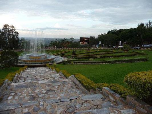 <b>Guillaume RUTEMBESA: Zentraler Kreisverkehr.</b> Um diesen Kreisverkehr und die abzweigenden Straßen erstreckt sich das kleine Stadtzentrum Kigalis. Der Platz in der Mitte mit Brunnen und Grünflächen wird Platz der Nationalen Einheit genannt.