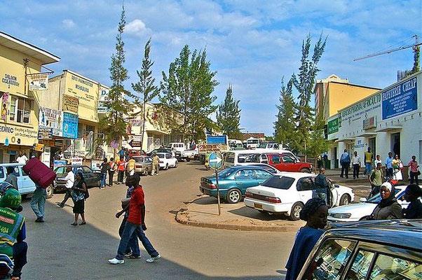 <b>Guillaume RUTEMBESA: Geschäftshäuser in Kigali.</b> Straßenszene. Vorne in der Mitte Fußgänger mit weißen Schuhen: Ruander/-innen putzen ihre Schuhe quasi täglich!