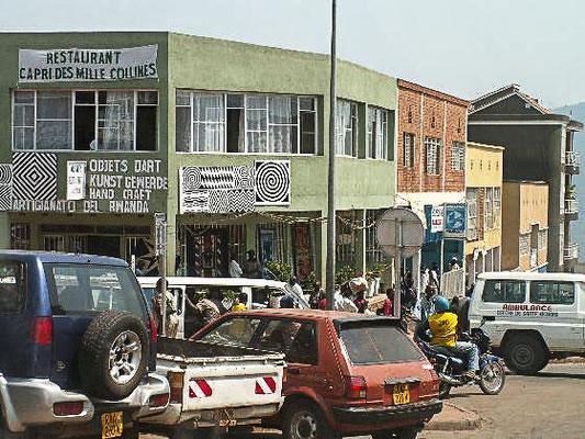 """<b>Guillaume RUTEMBESA: Geschäftsgebäude in Kigali. </b>Typische Straßenszene in Kigali. Der """"Kunst-Gewerbe""""-Laden an der Ecke wartet wohl auf deutschsprachige Besucher/-innen. Bei Kunsthandwerk ist Ruanda vor allem für seine Flechtarbeiten bekannt."""