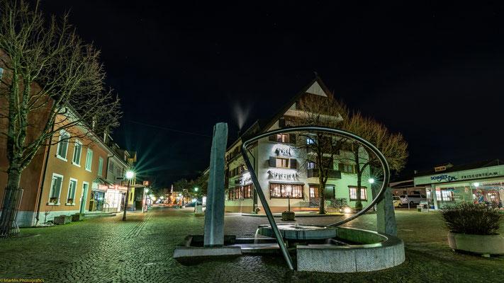"""Blick auf den Brunnen """"Zeitensegel""""  Richtung Hotel Fortuna in der Fußgängerzone"""