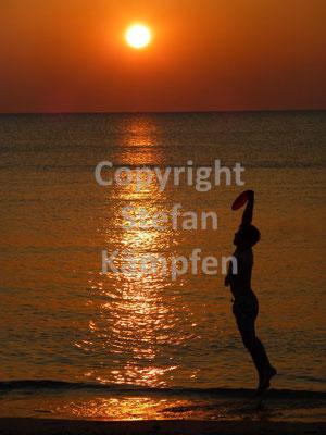Schönes Freizeitvergnügen: Frisbee Spielen während des Sonnenuntergangs