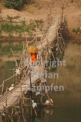 Ein buddhistischer Mönch schreitet über eine primitive Holzbrücke