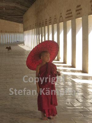 Junge in Möchskluft wandert durch die Säulenhalle eines Klosters