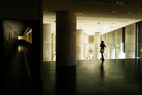 Mädchens, dessen Blick von der Ausstellung im unteren Bereich des Akropolis Museum gefesselt ist