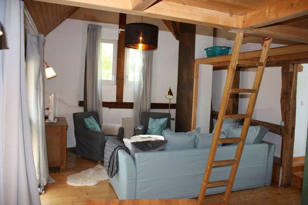 Wohnzimmer, mit  Leiter zum Schlafzimmerbereich auf der Empore