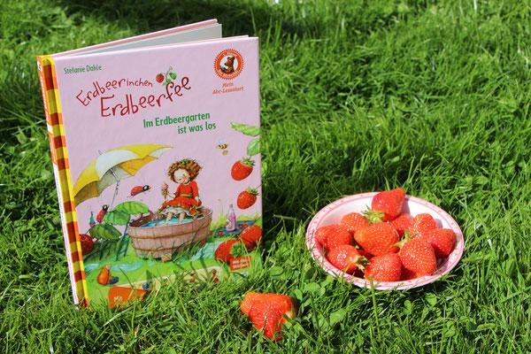 """Das Buch """"Erdbeerinchen Erdbeerfee - Im Erdbeergarten ist was los"""" mit eine Schale voll Erdbeeren"""