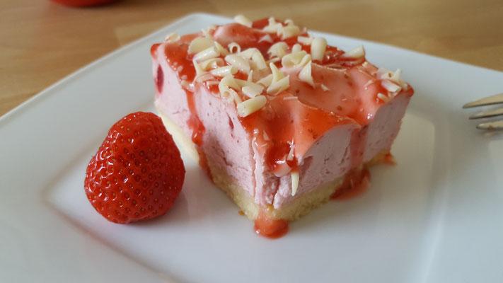 Ein Teller mit einem Stück Erdbeer-Sahne-Torte und einer Erdbeere