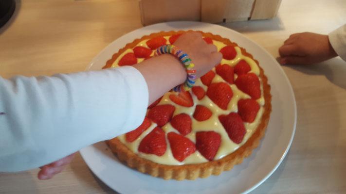Die Große legt Erdbeeren auf den Tortenboden mit Vanillepudding