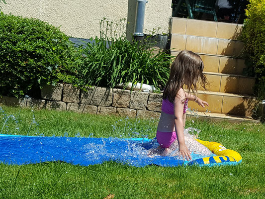 Unsere Kleine rutscht auf der Wasserbahn