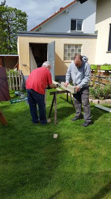 Opa und Stefan sägen die Latten und Füße für die Matschküche