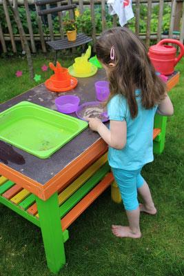 Unsere Kleine kocht in der selbstgebauten Matschküche im Garten