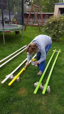 Doreen streicht die Latten für die Matschküche in gelb, grün und orange