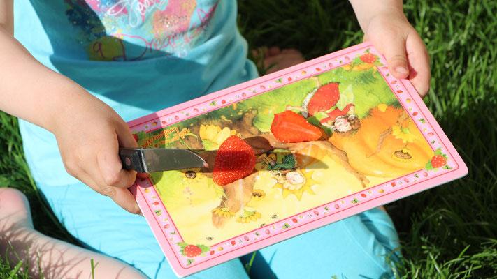 Unsere Kleine schneidet eine Erdbeere in zwei Teile