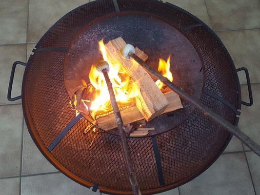 Unsere Große macht Marshmallows über der Feuerschale