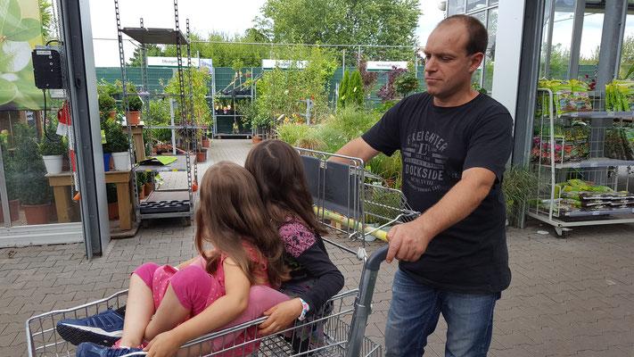 Die Mädels sitzen im Einkaufswagen im Dehner-Gartencenter