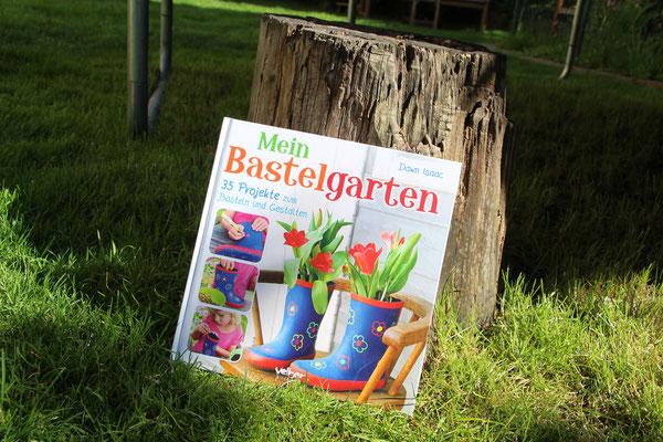 """Das Buch """"Mein Bastelgarten"""" lehnt an einem Baumstumpf"""