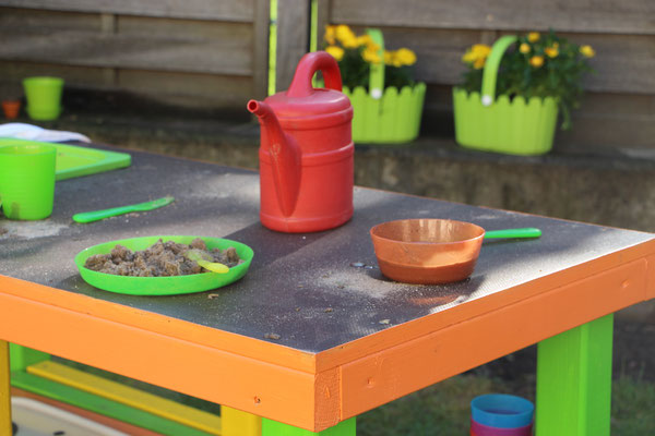 Schälchen voller Matsch auf der neuen Matschküche im Garten