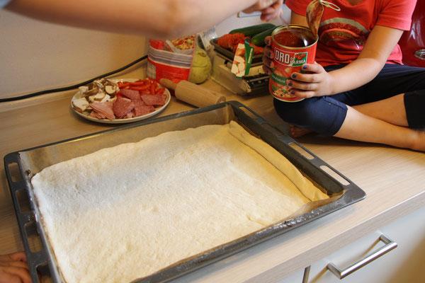 Der Pizzateig wartet auf seine Tomatensauce