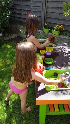 Unsere Mädels in in ihrer Matschküche im Garten