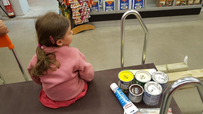 Unsere Kleine sitzt auf dem Baumaterial auf dem Einkaufswagen im Baumarkt