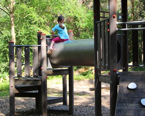 Unsere Kleine sitzt auf einem Klettergerüst am Braunshardter Tännchen
